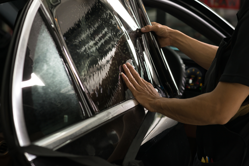 man applies window tint to car