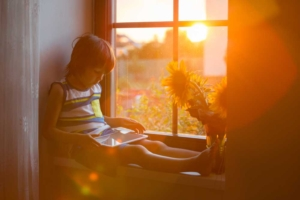 young boy sitting next to nook window with sun shining in